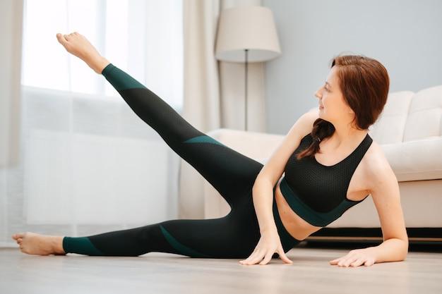 La giovane atleta si allena a casa sul pavimento con lo yoga per lo stretching e il tono muscolareconcetto di ...