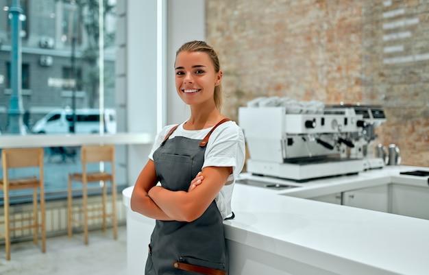 Giovane donna barista sta al bancone in una caffetteria e sorride.