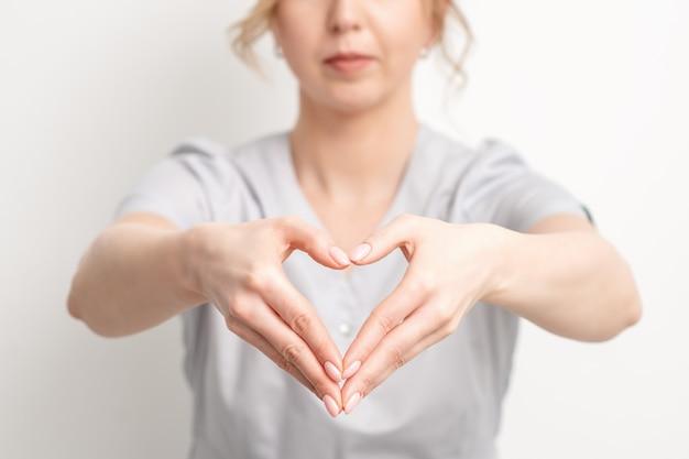 Giovane donna estetista che fa il cuore con la mano, da vicino.