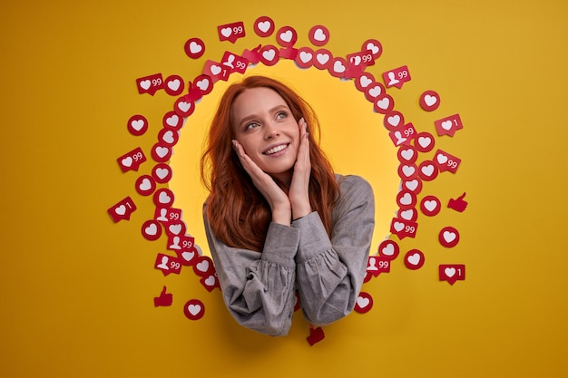 La giovane blogger è felice di ricevere molti mi piace e visualizzazioni, stare tra i pulsanti dei segni del cuore, eccitata e allegra, sorridente. ritratto