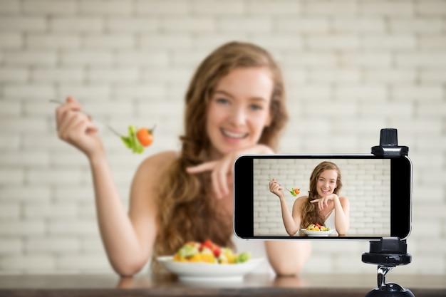 Giovane blogger e vlogger e influencer online in diretta streaming uno show di cucina sui social media utilizzando uno smartphone