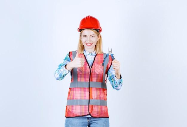 Il giovane maestro biondo femminile in una camicia a strisce blu sta facendo un segno simile mentre tiene le pinze davanti al muro bianco