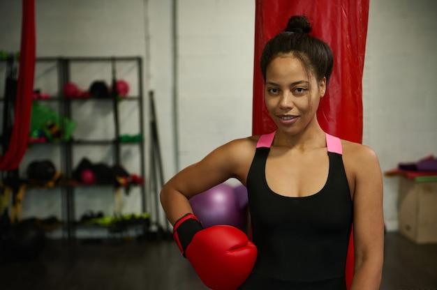 Giovane pugile femminile, ragazza sportiva, donna atleta, donna sportiva, che indossa guanti da boxe rossi, guarda la telecamera in posa contro l'attrezzatura sportiva in palestra