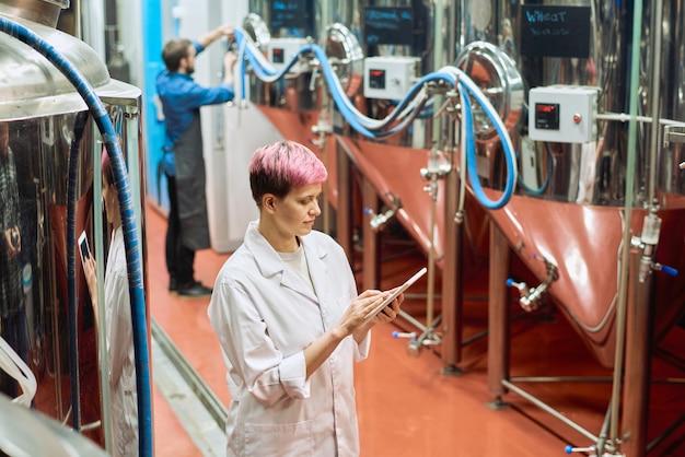 Giovane esperta di birrificio femminile che esamina i dati nella tavoletta digitale mentre è in piedi accanto a nuove attrezzature per la produzione di birra contro un lavoratore di sesso maschile