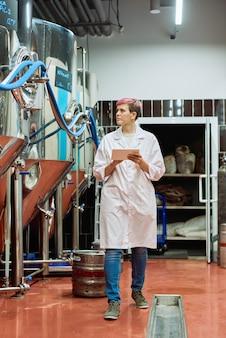 Giovane esperta di birra in camice bianco che inserisce dati nel tablet mentre si muove lungo un'enorme nuova attrezzatura in acciaio per la produzione di birra nello stabilimento