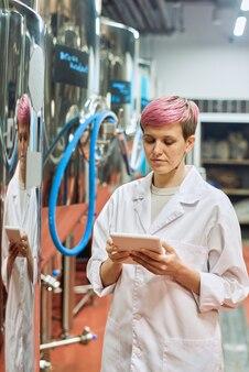 Giovane esperta di birrificio femminile in camice bianco che esamina i dati nella tavoletta digitale mentre è in piedi accanto a nuove attrezzature per la produzione di birra nello stabilimento