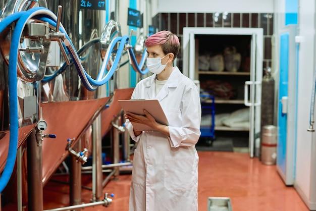 Giovane esperta di birrificio femminile in camice bianco e maschera protettiva che prende appunti mentre guarda nuove attrezzature in acciaio per la produzione di birra