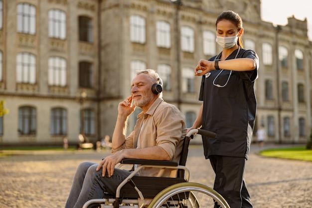 Giovane assistente femminile in maschera protettiva che trascorre del tempo con un uomo anziano in sedia a rotelle che indossa