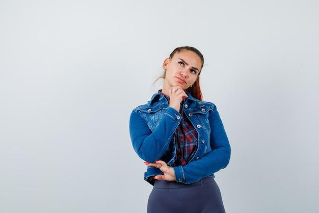 Giovane donna in camicia a scacchi, giacca, pantaloni alzando lo sguardo e guardando premurosa, vista frontale.
