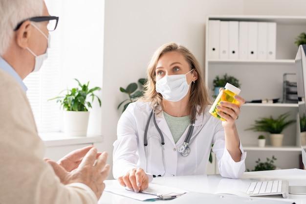 Giovane medico femminile nella maschera protettiva che tiene la bottiglia con le pillole mentre mostra e li raccomanda al paziente in ospedale