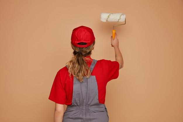 Giovane operaio edile femminile che indossa il cappello e uniforme in piedi dietro la vista che allunga il rullo di vernice