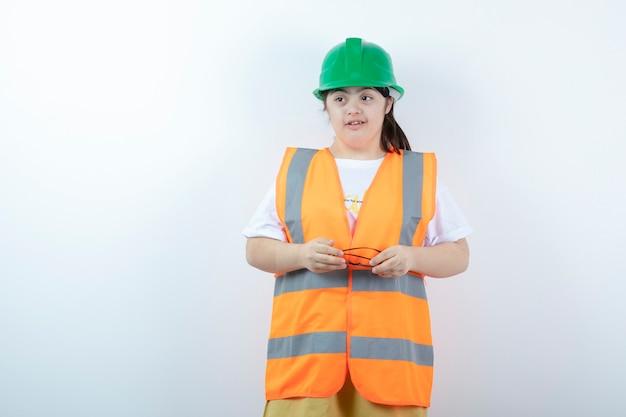 Giovane operaio edile femminile che indossa i suoi occhiali sul muro bianco
