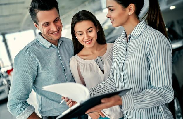 Giovane consulente femminile e coppia di acquirenti che firmano un contratto per una nuova auto al salone dell'auto. concetto per il noleggio auto.