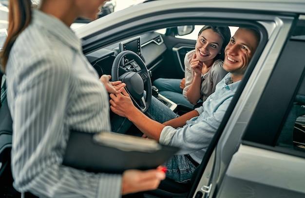 Giovane consulente femminile e compratori delle coppie che si siedono nel contratto di firma di automobile nuova nel salone dell'auto. concetto per il noleggio auto.