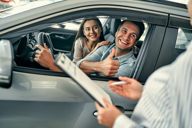 Giovane consulente femminile e compratori delle coppie che si siedono nel contratto di firma di automobile nuova nel salone dell'auto. un uomo mostra un pollice in alto a un consulente. concetto per il noleggio auto.
