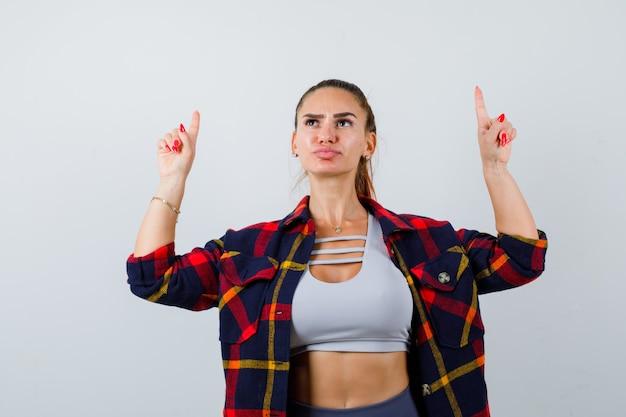 Giovane donna in crop top, camicia a scacchi, pantaloni che puntano verso l'alto e sembrano pensierosi, vista frontale.