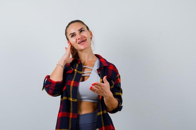 Giovane donna in crop top, camicia a scacchi, pantaloni con la mano sull'orecchio mentre mostra qualcosa e sembra felice, vista frontale.