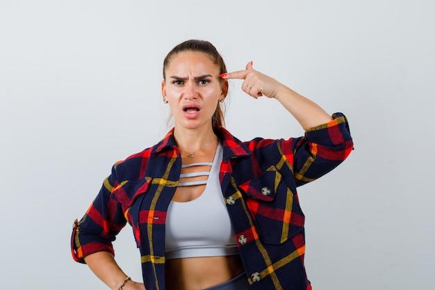 Giovane donna in crop top, camicia a scacchi che punta alla testa e sembra perplessa, vista frontale.