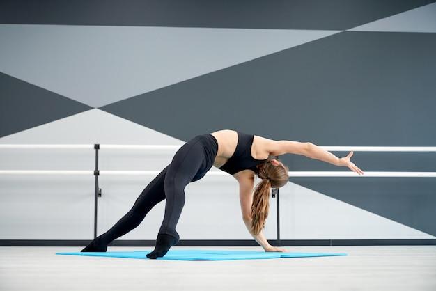 Giovane ballerina femminile che si estende sul pavimento