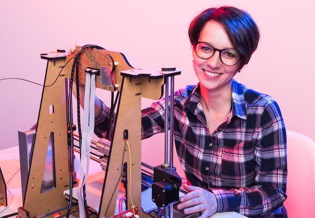 Giovane ingegnere progettista femminile che utilizza una stampante in laboratorio e studia un prototipo di prodotto, un concetto di tecnologia e innovazione.