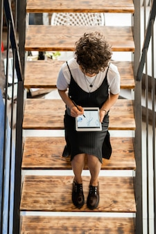 Giovane designer femminile con tavoletta digitale e penna facendo schizzi di nuovi modelli di moda mentre è seduto sulle scale