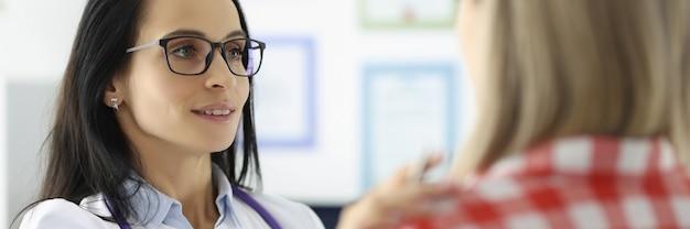 Giovane dottoressa che tiene il paziente per spalla in clinica assistenza medica psicologica