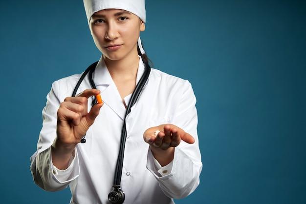Giovane dottoressa in possesso di una pillola, guardandola e dandola come trattamento per il paziente