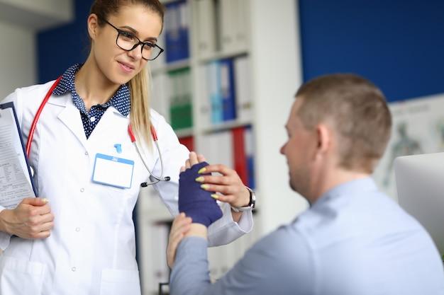 Il giovane medico femminile sta aiutando il paziente