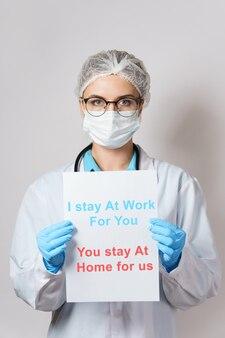 La giovane dottoressa tiene in mano la carta con l'appello alle persone durante la quarantena