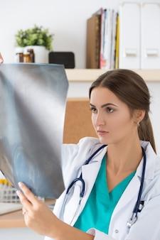 Giovane medico femminile che esamina l'immagine dei raggi x dei polmoni