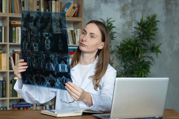Una giovane dottoressa guarda i raggi x mentre è seduto in un ufficio in una clinica