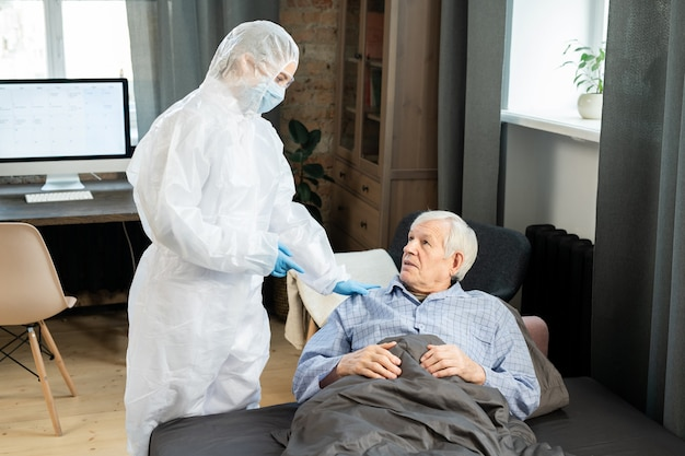 Giovane dottoressa in tute protettive che tocca la spalla di un uomo anziano malato sdraiato sul divano sotto la coperta e gli dà consigli medici