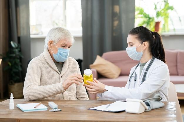 Giovane dottoressa in camice bianco e maschera protettiva che tiene una bottiglia di pillole sul tavolo, mostrandole e prescrivendole a un uomo anziano malato