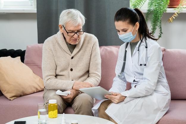 Giovane dottoressa in camice bianco e maschera protettiva che tiene in mano una tavoletta digitale mentre è seduta sul divano accanto a un uomo anziano malato e lo consulta