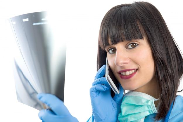 Giovane medico femminile con il telefono che esamina i raggi x dei pazienti