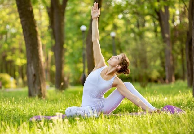 Giovane femmina che fa allungamento ed esercizio di yoga su erba nel parco