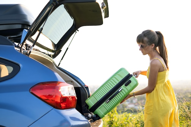 Giovane autista femminile che mette la valigia verde all'interno del bagagliaio dell'auto. concetto di viaggi e vacanze.