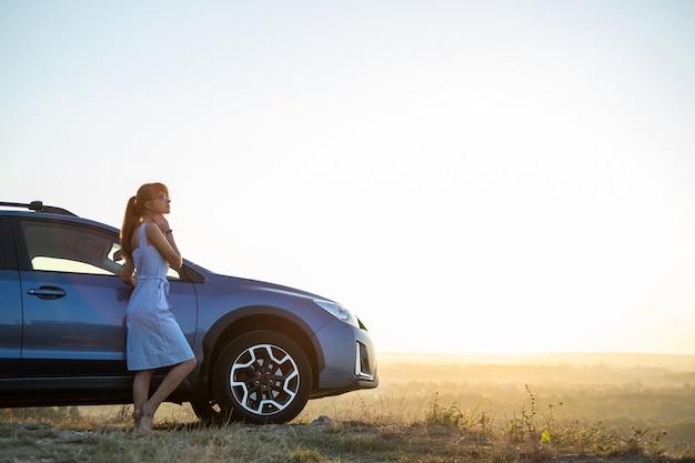 Giovane autista femminile che riposa vicino alla sua auto godendosi la calda serata estiva. concetto di viaggio e fuga.