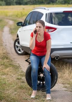 Giovane autista donna seduta accanto all'auto rotta al campo e parlando al telefono