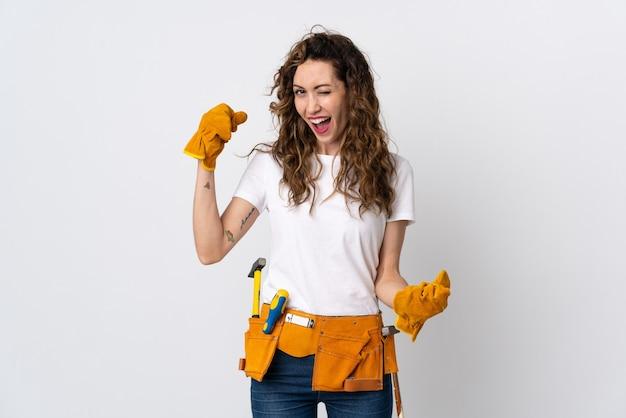 Giovane elettricista femminile isolato sulla parete bianca che celebra una vittoria