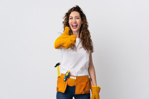 Giovane elettricista femminile isolato sul muro bianco con i pollici in su perché è successo qualcosa di buono