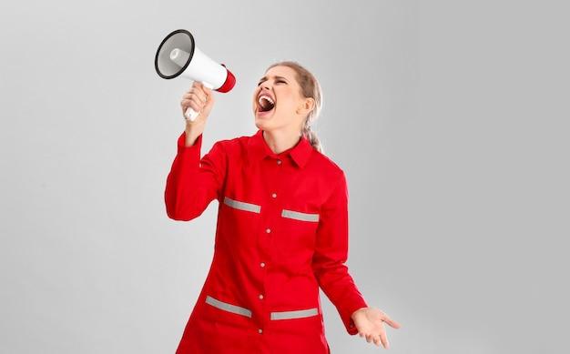 Giovane medico di emergenza femminile che grida nel megafono su gray