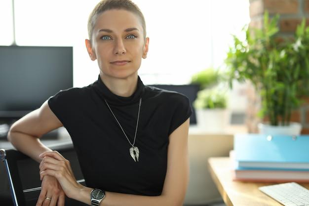 Giovane impiegato femminile è seduto a un tavolo in ufficio appoggiando la mano su una sedia. ragazza creativa in posa sul lavoro