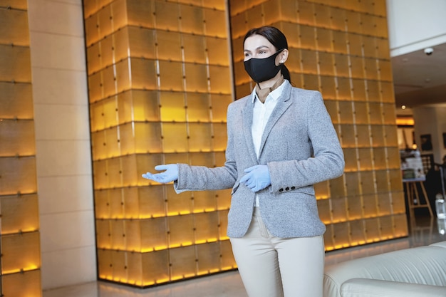 Giovane impiegata che indossa una maschera e guanti di gomma mentre mostra la strada per le stanze. banner del sito web