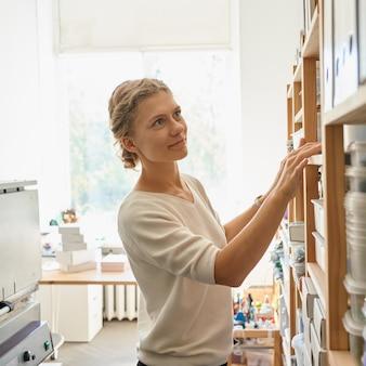 Giovane imprenditore femminile alla ricerca sugli scaffali per i prodotti