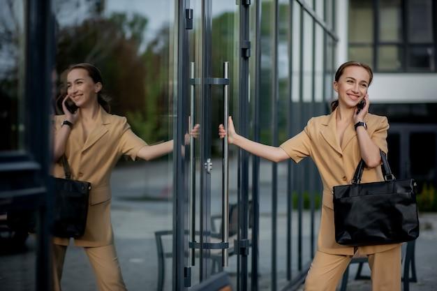 Giovane dirigente femminile in piedi fuori dall'edificio per uffici a parlare sul telefono cellulare.