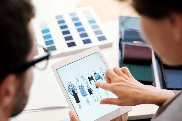 Giovane stilista femminile che punta a uno degli schizzi di modello sul touchscreen mentre ne discute con il collega