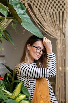 La giovane fiorista femminile gode della cura delle piante calma imprenditrice freelance imprenditrice nel giardino di casa