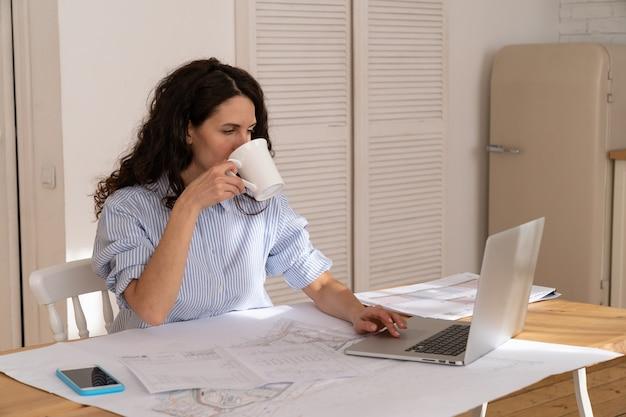 La giovane donna freelance beve il caffè al tavolo lavora in remoto sul laptop