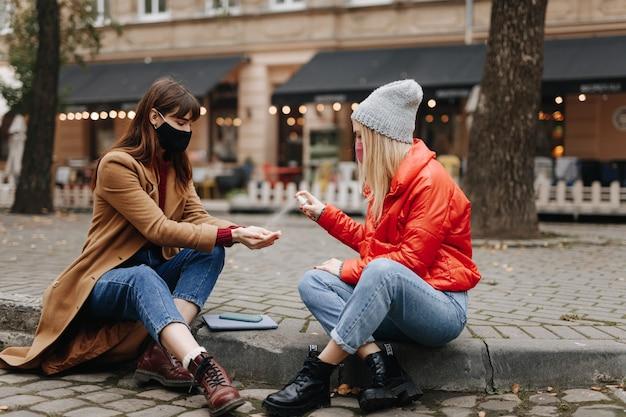 Giovani amici di sesso femminile in maschere di igiene medica spruzzare le mani con antisettico mentre era seduto in una strada di città. protezione dalle malattie infettive.
